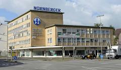 Architektur der 1960er Jahre in Wilhelmshaven, Bürogebäude einer Versicherung mit gelber Ziegelfassade und Geschäftszeile.