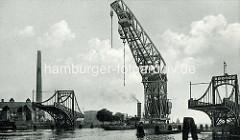Historische Fotografie von einem Schwimmkran, der die geöffnete Kaiser Wilhelm Brücke / Drehbrücke durchfährt.