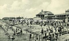 Historische Fotografie vom Badegeschehen am Südstrand in Wilhelmshaven; Holztreppen führen vom Deich ins Wasser Strandkörbe stehen am Ufer.
