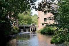 Blick über den Fluss Böhme zum Stauwerk / Wasserrad der alten Waldmühle am Mühlenweg in Soltau.