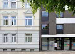 Architektur in Wilhelmshaven, alt und neu nebeneinander; links die Hausfassade eines Gründerzeitwohnhauses, rechts  ein Neubau mit quadratischen Fenstern und Ladenzeile.