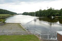 Ein Sportboot hat die Schleuse am Maadesiel in Wilhelmshaven passiert und fährt in die Maade ein.