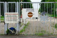 Metalltor vom Marinearsenal in Wilhelmshaven / Tor mit Metalladler; Hinweisschild Achtung Tor geschlossen - militärischer Sicherheitsbereich, Vorsicht Schusswaffengebrauch.