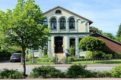 Historische Architektur in der Butjadinger Straße von Burhave - Wohnhaus mit halbrunden Fenstern und Säulen, farblich abgesetzt.