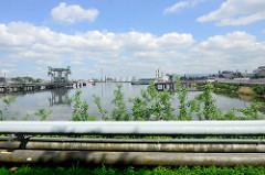 Blick auf den Kattwykhafen - Tankhafen in Hamburg Wilhelmsburg; im Vordergrund verlaufen Pipelines - im Hintergrund Tankanlagen.