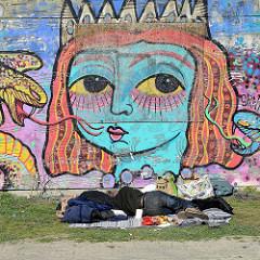 Wandbild am Hafen von Münster - schlafender Mensch auf einer Decke in der Sonne.
