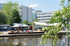 Kanalisierter Lauf der Alster  bei Hamburg Eppendorf; Beachclub am Alsterufer, dahinter Bürogebäude.