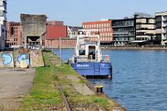 """Alte Gleise an der Südseite vom Alten Hafen in Münster - auf der Nordseite die Neubauten vom Kreativkai; das Boot """"Münster"""" der Wasserschutzpolizei hat am Kai festgemacht."""