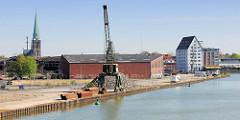Blick auf den Dortmund-Ems-Kanal in Münster - Hafenkran am Kanalufer; im Hintergrund Gebäude am Münsteraner Hafen und der Kirchturm der Hl. Kreuzkirche.