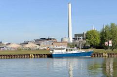 Sportboot beim Dortmund-Ems-Kanal in Münster - Brachland und Industriegebäude, stillgelegter Fabrikschornstein.