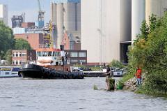 Schlepper auf dem Reiherstieg in Hamburg Wilhelmsburg - im Hintergrund Silo-Anlagen, Angler am Ufer.