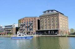 Umgenutzte alte Speichergebäude im Hafen von Münster / Kreativkai  - das Boot WSP 36 der Wasserschutzpolizei Münster in Fahrt.