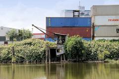 Alter Kran am Ufer des Schmidtkanals in Hamburg Wilhelmsburg; dahinter Containerstapel.