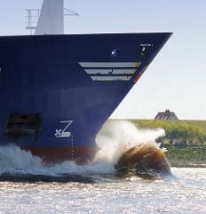 Wulstbug eines Container Feeders auf der Elbe bei Hamburg - Gischt sprüht hoch auf; im Hintergrund ein Hausdach hinter dem Elbdeich.