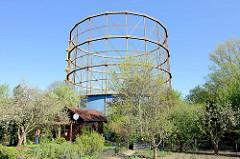 Gasometer in Münster, errichtet 1954 - stillgelegt 2005; die Glockenkonstruktion des Teleskopgasbehälters steht als technisches Denkmal unter Denkmalschutz. Im Vordergrund eine Kleingartenanlage mit Obstbäumen und Schrebergartenhaus.