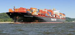 Der Containerfrachter Tsingtao Express  fährt mit Containern hoch beladen auf der Elbe; das 335 m lange Frachtschiff kann 8600 TEU Container transportieren.
