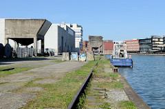 """Alte Gleise und Schüttgutanlage an der Südseite vom Alten Hafen in Münster - auf der Nordseite die Neubauten vom Kreativkai; das Boot """"Münster"""" der Wasserschutzpolizei hat am Kai festgemacht."""