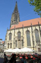 Lamberti Kirche in Münster, erbaut zwischen 1375 und 1525; Aussengastronomie mit Tischen unter Sonnenschirmen auf dem Kirchplatz / Salzstraße.
