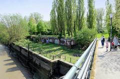 Fussgängerbrücke über das Hafenbecken Haken in Hamburg Rothenburgsort, Elbpark Entenwerder; Reste der Kaimauer und alten Hafen / Zollanlagen sind zu erkennen.