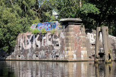 Reste eines Brückenfundaments am Tiefstackkanal in Hamburg Rothenburgsort / Billbrook, die Mauern sind mit Graffiti bemalt; re. ein alter Holzdalben zum Festmachen von Schiffen.