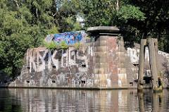 Reste eines Brückenfundaments am Tiefstackkanal in Hamburg Rothenburgsort / Billbrook, die Mauern sind mit Graffiti bemalt; re. ein alter Holzdalben zum Festmachen von Schiffen.