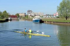 Ruderboot auf dem Dortmund-Ems-Kanal in Münster - Hafenbecken mit Sportbooten und Brachland.