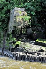 Ruine einer Kaimauer im Hamburger Hafen - Reste der Steinmauer mit Wildkraut; unten die Holpfähle, auf dem die Kaianlage ruht - sie liegen bei Niedrigwasser frei.