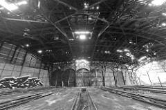 Einfahrten / Türen - teilweise zugemauert - eines Ringschuppens der Eisenbahn; Schienenanlage mit Grube für Arbeiten unter der Lokomotive. Das Dach des Lokschuppens ist stark verfallen.