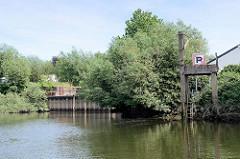 Spundwand - Hochwasserschutzanlage bei der historischen Schleuse vom Schmidtkanal in Hamburg Wilhelmsburg; re. eine alte Verladestelle auf Betonstelzen mit Handkran.