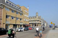 Blick in die Stationsstraat  von Maastricht; im Hintergrund die historische Architektur vom Amrâth Grand Hotel de l'Empereuram Hauptbahnhof der Stadt - im Vordergrund  ein Wohnhaus / Geschäftshaus mit gelber Ziegelfassade.