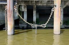 Eisenpfeiler mit Eisenketten an einer stillgelegten Anlegestelle im Hamburger Hafen.