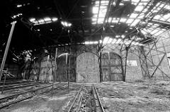 Türen - teilweise zugemauert - eines Ringschuppens der Eisenbahn; Schienenanlage mit Grube für Arbeiten unter der Lokomotive. Das Dach des Lokschuppens ist stark verfallen.