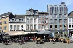 Marktplatz von Roermond, historische Wohnhäuser / Geschäftshäuser. Auf dem sonnigen Platz haben Restaurants und Cafés Tische und Stühle in die Sonne gestellt.