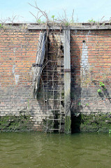 Alte rostige Kaitreppe - Eisentreppe an einer Ziegelmauer / Hafenkai im Hamburger Hafen. Links und rechts zwei Streichdalben aus Holz, die Treppe vor den Bordwänden der anlegenden Schiffe schützen sollten.