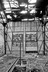 Ruine eines Lokschuppens - das Dach ist verfallen, mit großen Löchern - Fenster sind vernagelt.