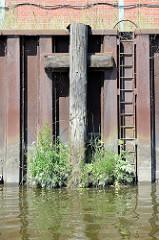 Verwitterter Streichbalken aus Holz an einer stillgelegten Kaianlage im Hamburger Hafen; Wildkraut wächst aus dem alten Holz der Balken - ein sogen. Streichbalken schützt die Kaianlage vor direkten Kontakt mit Schiffswänden. Daneben eine Eisenlei