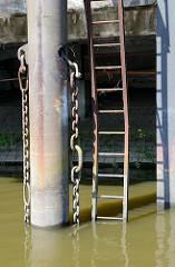 Eisenpfeiler mit dicker Kette - verbogene Eisenleiter, die zu einer stillgelegten Kaianlage im Hamburger Hafen führt.