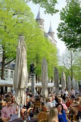 Straßencafé unter Bäumen auf dem Onze Lieve Vrouweplein in Maastricht - im Hintergrund Spitzen der Kirchtüme von der Liebfrauenbasilika.