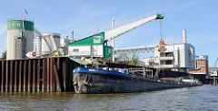 Verladestation mit Kran an der Norderelbe in Hamburg Wilhelmsburg - die Ladung von  einem Binnenschiff wird gelöscht.