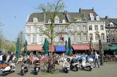 Mehrstöckige Wohn- und Geschäftshäuser am Markt von Maastricht; Restaurants und Cafés haben Tische und Stühle Straße gestellt - die Plätze sind dicht besetzt, die Gäste sitzen in der Sonne.