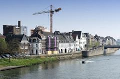 Wohnhäuser am Ufer der Maas Maastricht, ein Motorboot fährt flussaufwärts.