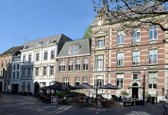 Wohnhäuser / Geschäftshäuser in unterschiedlichen Baustil in der Straßeparade von Venlo; Restaurant mit Tischen und Stühlen auf der Straße / Sonnenschirme.