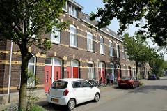Einstöckiger  Wohnblock - geschlossene  Straßenbebauung mit roter Backsteinfassade und gelben  Zierbändern in der Van Den Berghstraat in Maastricht.