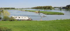 Blick über die Maas zum Schiffershaven in Roermond - ein Hausboot liegt am Ufer vom Donkernack - Sportboote fahren auf dem Fluß.