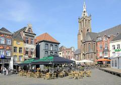 Marktplatz von Roermond, historische Wohnhäuser / Geschäftshäuser; dahinter die Christophorus Kathedrale / Christoffelkathedraal in Roermond; Baubeginn 1410 - Fertigstellung  im 16. Jahrhundert. Auf dem sonnigen Platz haben Restaurants und Cafés