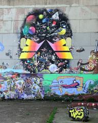 Graffiti an der Hausmauer eines alten Fabrikgebäudes im  Hafengebiet von Maastricht.
