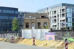 Neubaugebiet  auf einem alten Fabrikgelände am Heugemerweg  in Maastricht  - ein kleines freistehendes Gebäude im Vordergrund wird noch bewohnt.
