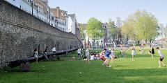 Alte Stadtmauer und historische Kanonen in Maastricht - Jugendliche spielen Fussball, Kinder sitzen auf den Kanonenrohren.