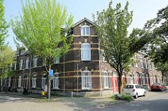Eckgebäude, einstöckiger  Wohnblock - geschlossene  Straßenbebauung mit roter Backsteinfassade und gelben  Zierbändern in der Van Den Berghstraat in Maastricht.