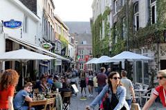 Fussgängerzone in der Koestraat  von Maastricht - Gäste von Cafés und Restaurant sitzen an Tischen auf der Straße.